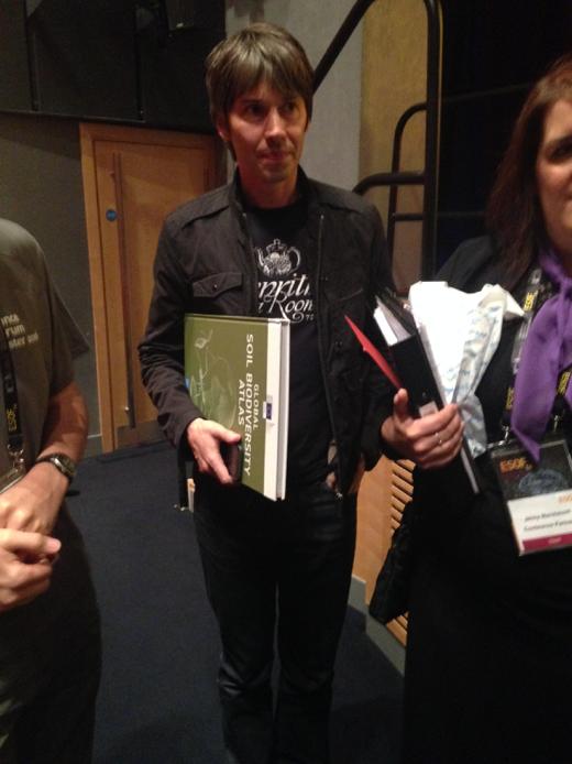 Brian Cox holding Global Soil Biodiversity Atlas.   Photo credit A. Orgiazzi