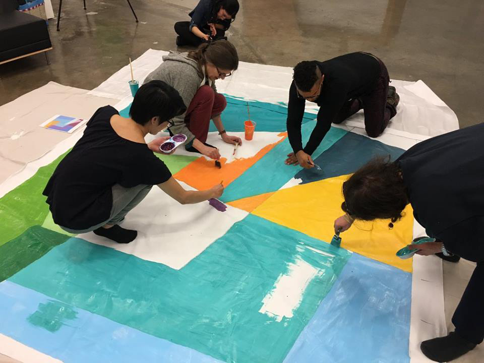 Art Break program occurring in the lobby of Express Newark, in the Hahnes Building. The workshop is being led by artist Kati Vilim and participants are working on large versions of paintings inspired by her work. Vilim is the first Artist in Residence for Paul Robeson Galleries.