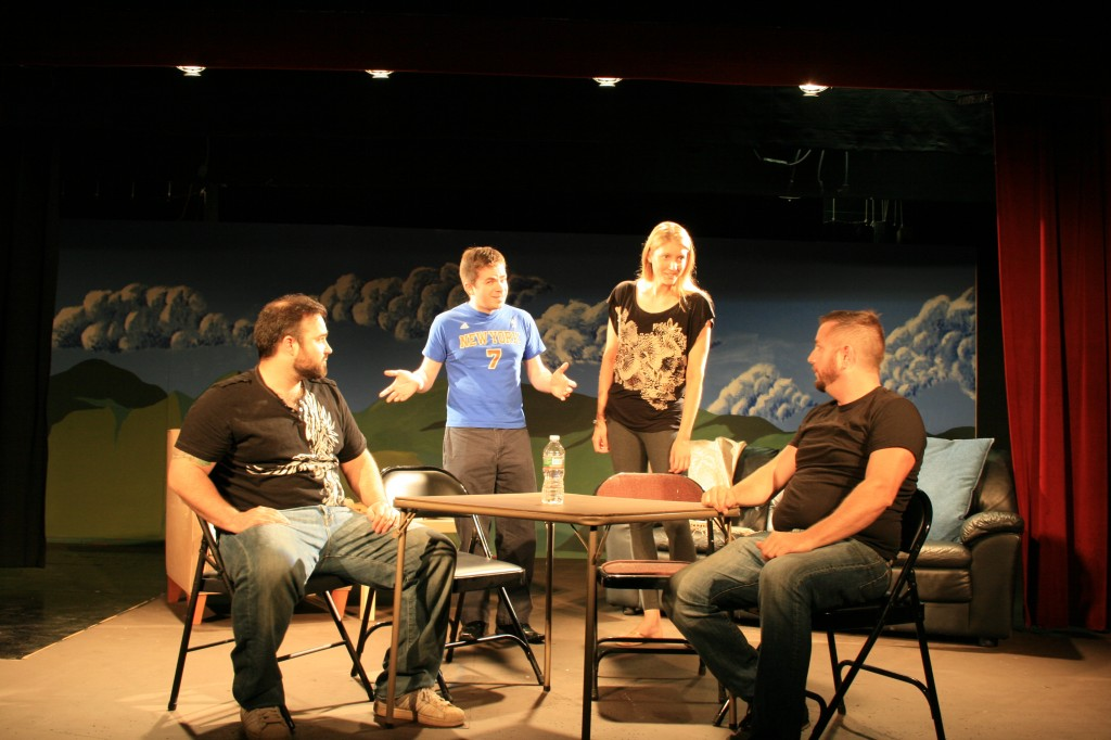 Jake (Tim Moran), far right, tries to explain the importance of jigsaw puzzles to his friends (l to r, Damian Gaeta, Patrick Lavery, Michelle Wood, and on the couch, Emily O'Sullivan) in Puzzle Theory