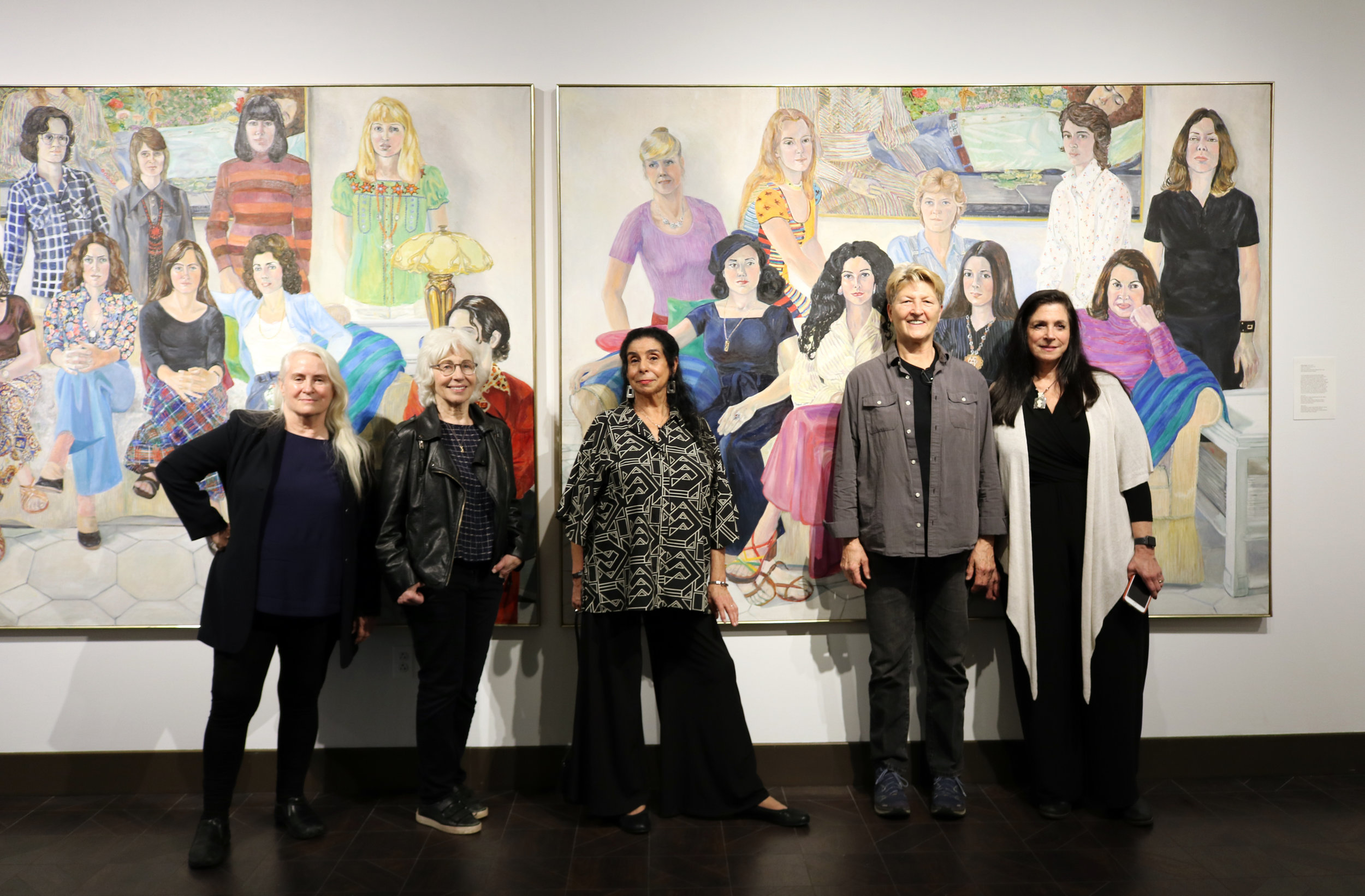 "Painting: Sylvia Sleigh (1916–2010), ""SOHO 20 Group Portrait,"" 1974, oil on two canvases. Collection of the University of Missouri–St. Louis, Gift of Robert and Lois Orchard.  Artists/others pictured in front of the painting: Sharon Wybrants, Elena Borstein, Cynthia Mailman, Marge Helenchild, and Rosalind Shaffer."
