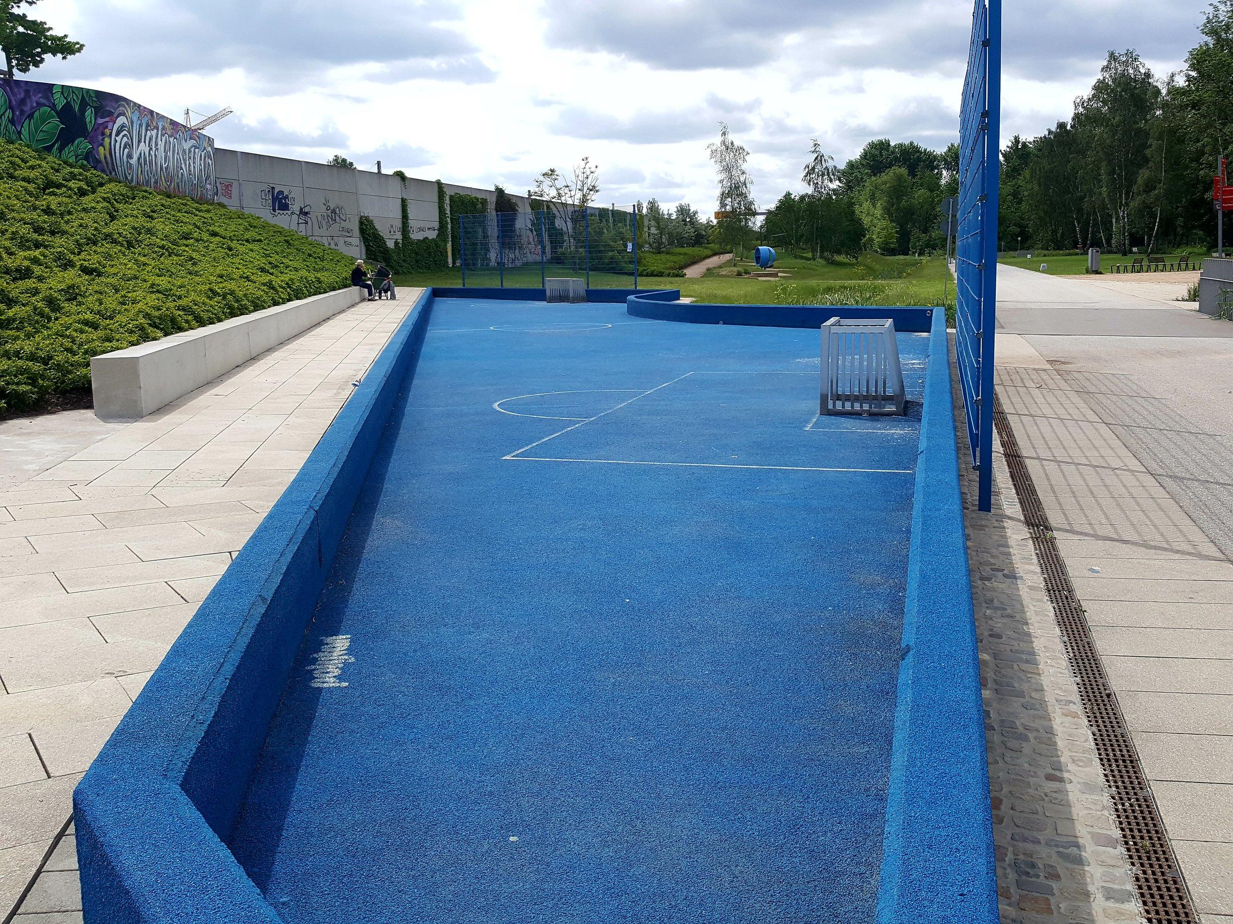 Ikke alle tyske idrætsmiljøer er firkantede. I Welt der Bewegung fyldes den skæve fodboldbane tilmed med vand i ankelhøjde om sommeren.  Foto. Henrik H. Brandt