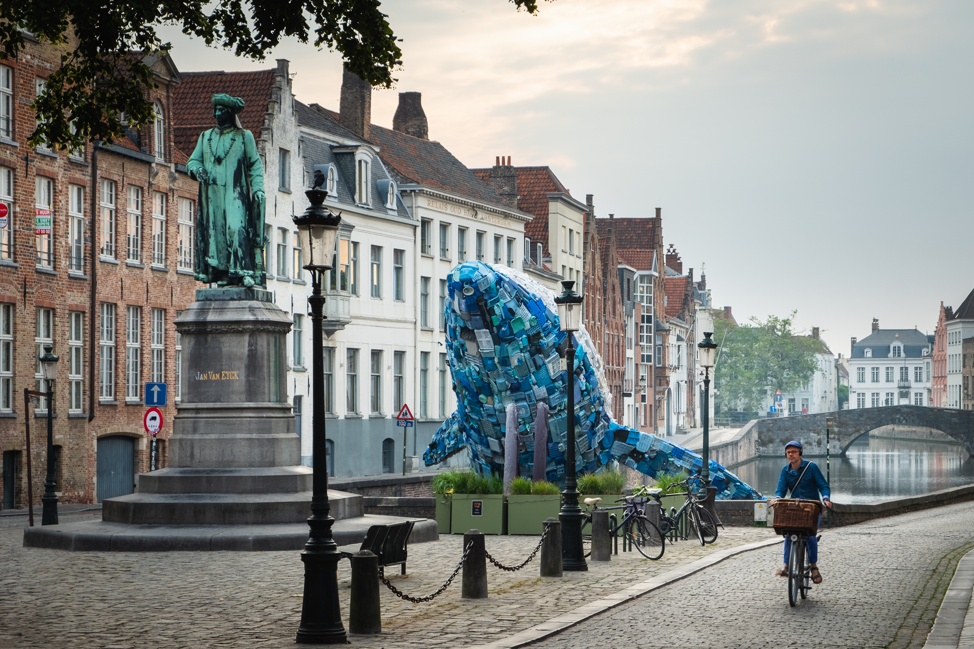 A photo of the Skyscraper and the statue of Jan van Eyck at along the canal in Bruges , Belgium taken by Trevor Sherwin