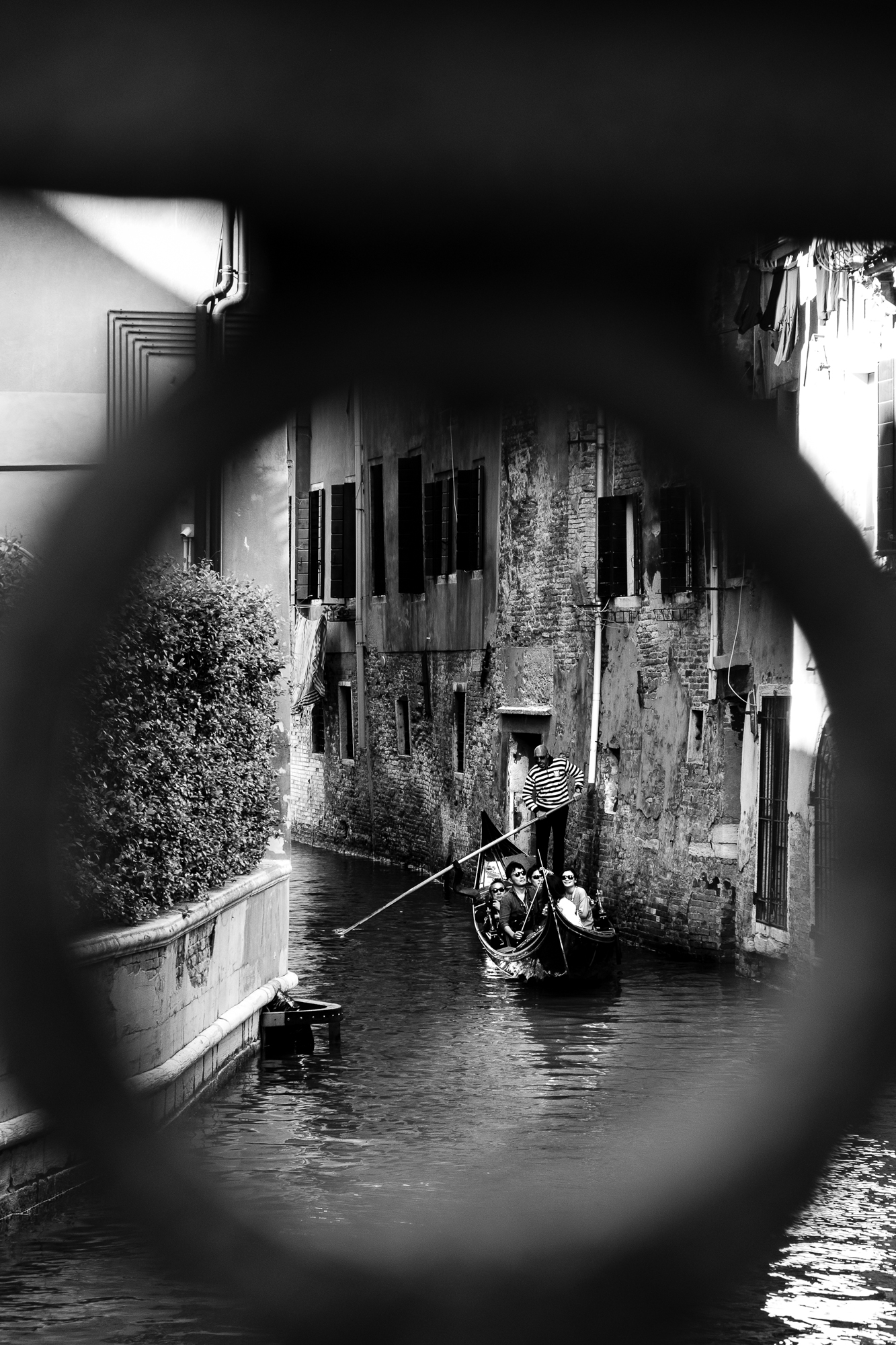 A photo of a Gondolier on the canal in Venice shot through a hole taken by Trevor Sherwin