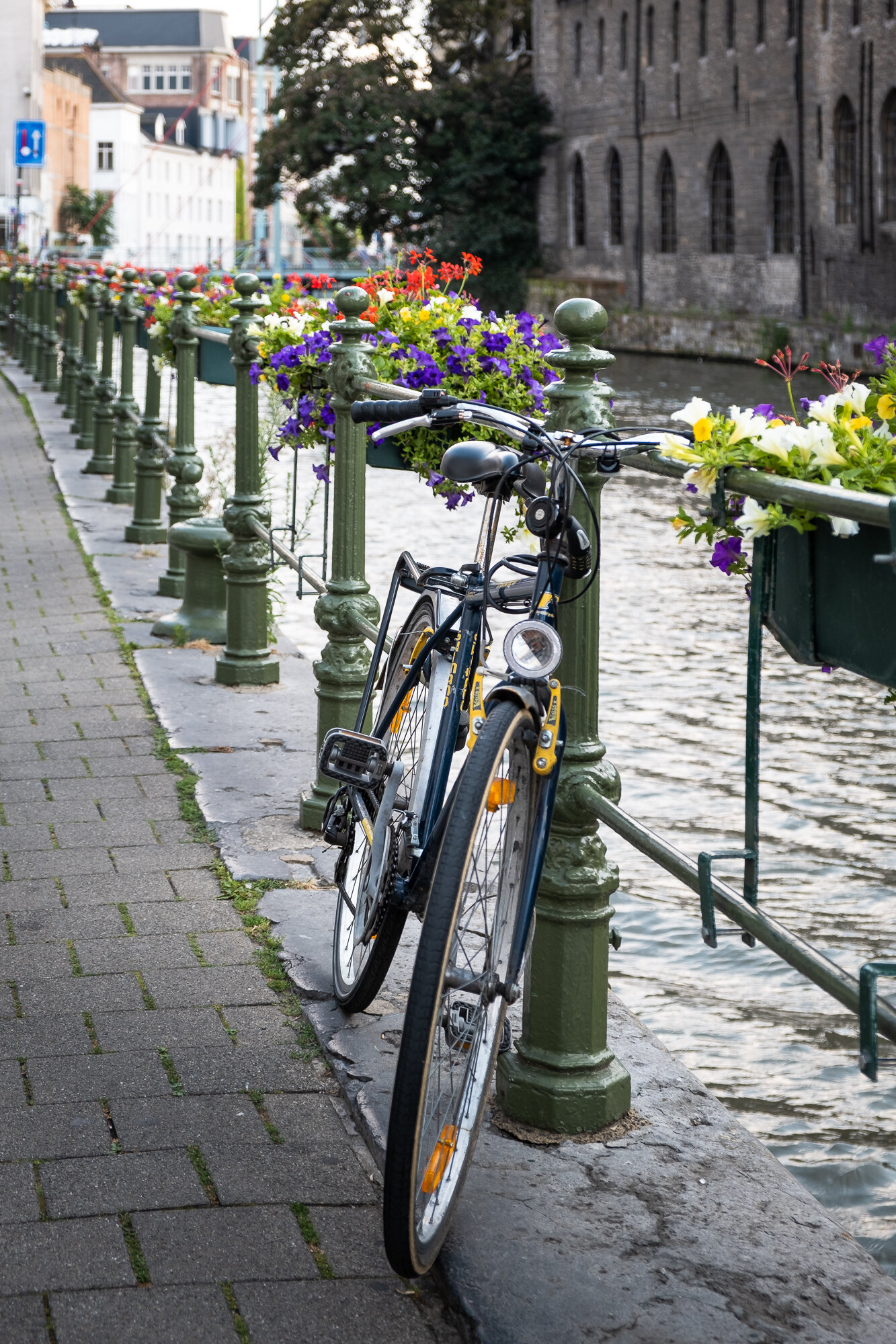 A bike on the railings in front of the River Leie