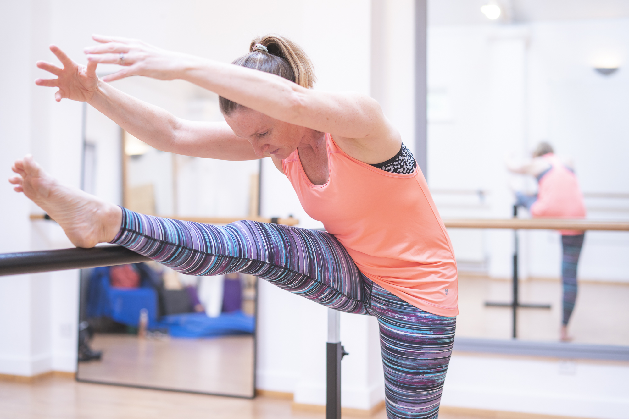 Stretches performed on the ballet barre. Body of a dancer and strength and toning.