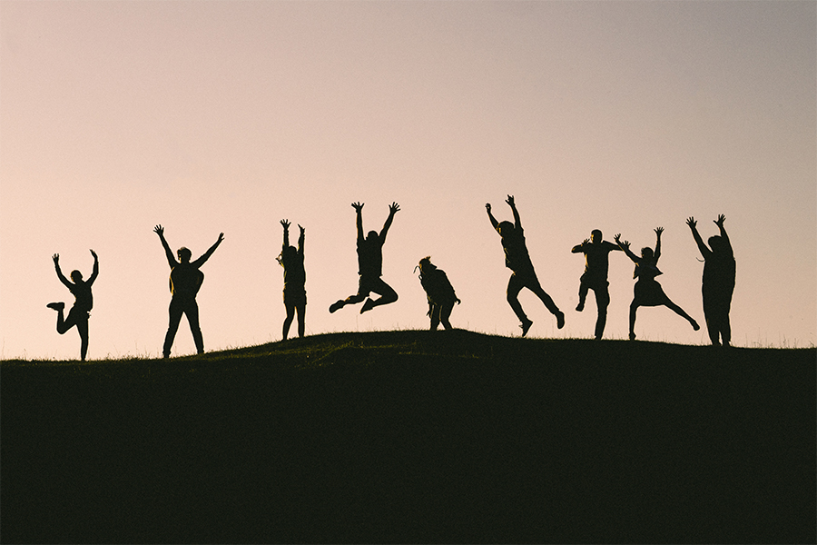 people jumping on a hill with the sunset behind