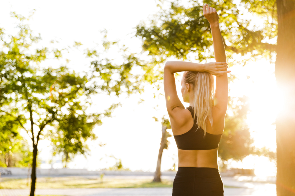 Back view photo of beautiful young blonde sports woman in park outdoors make stretching exercises.jpg