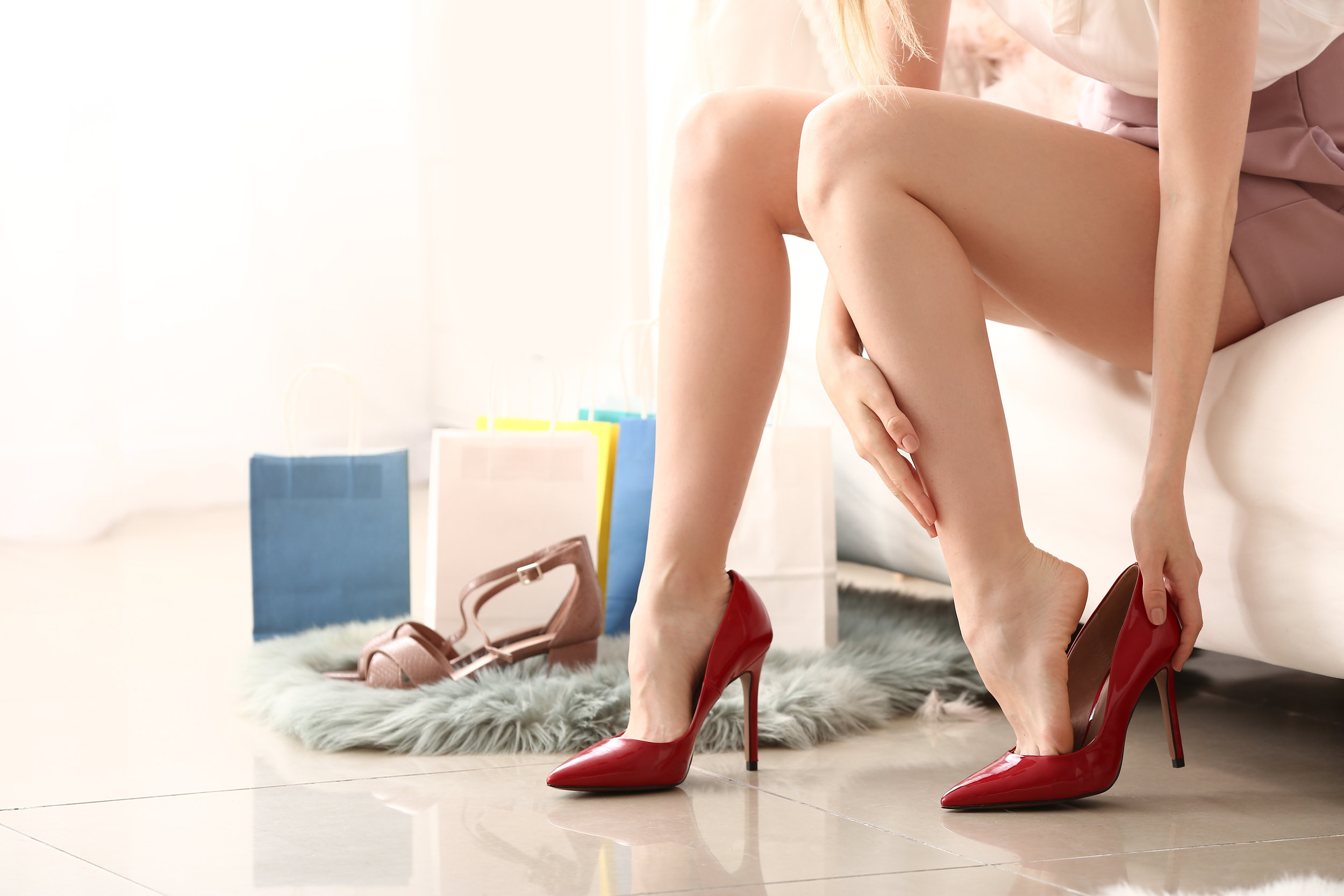 Young woman taking off high-heeled shoes at home