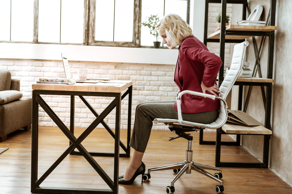 Constant sitting. Unhappy beautiful lady in office outfit and high heels touching her back because of pain