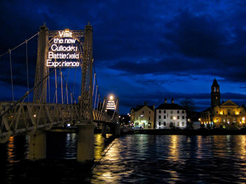 The River Ness by night, proclaiming in neon the worst taste in Tartan Tourism.