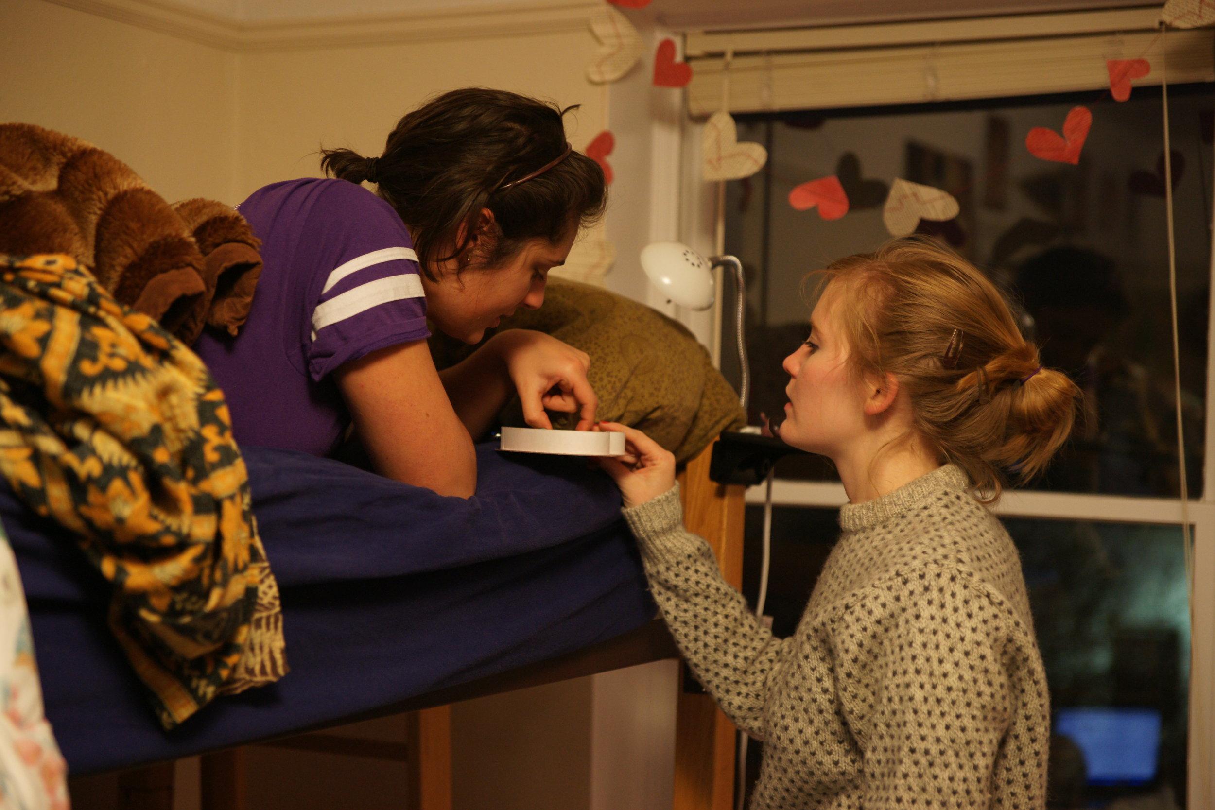 Emily feeding Jess chocolates in bed.