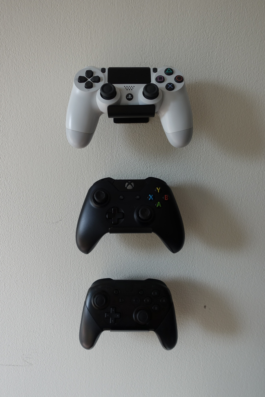Mounted gaming console controllers for PS4, XBox, and Nintendo Switch.