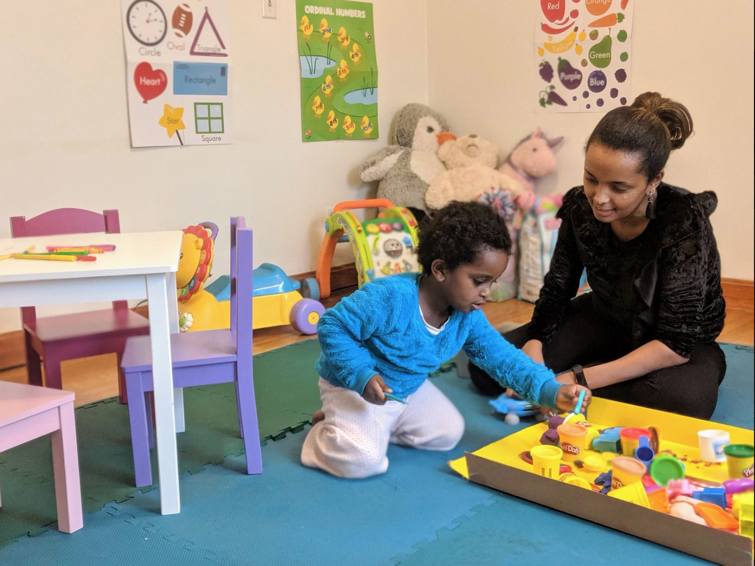 Silenat plays with a child in her new daycare in Revere, MA.