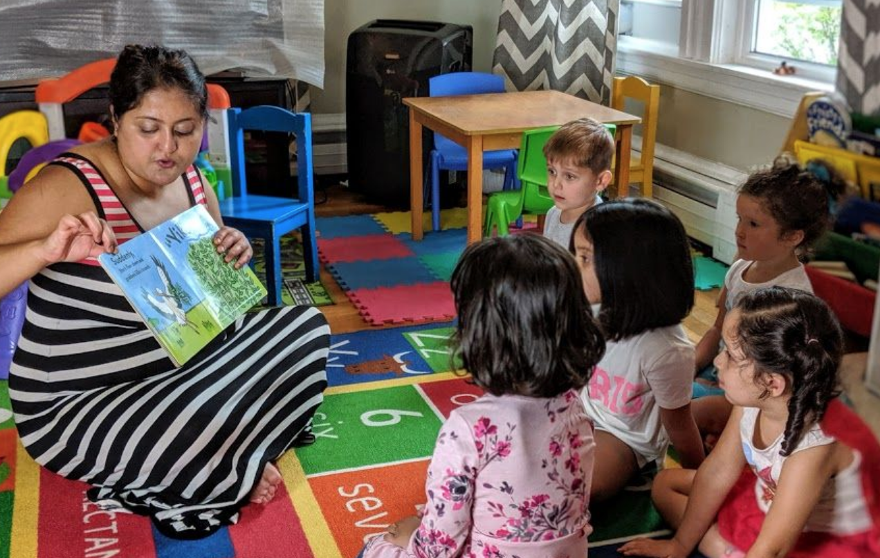 Ms. Kate reads to children at her daycare in North Andover, MA.