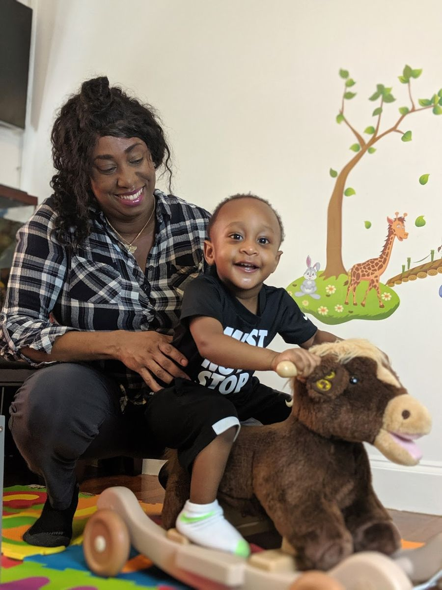 Ms. Latoya plays with a child at her home daycare in Mattapan, MA.