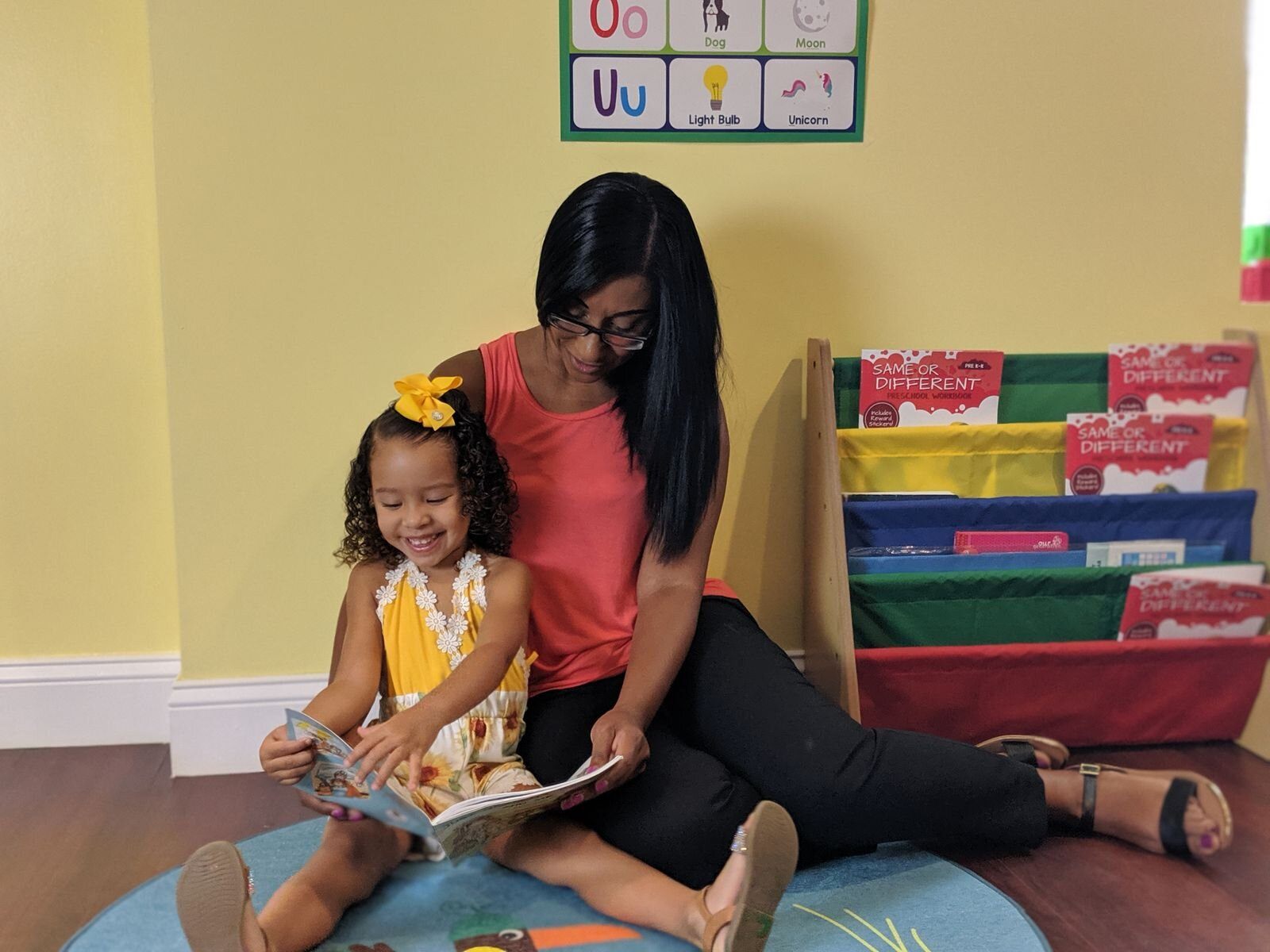 Ms. Jocie reads a book to a child at her daycare in Taunton, MA.