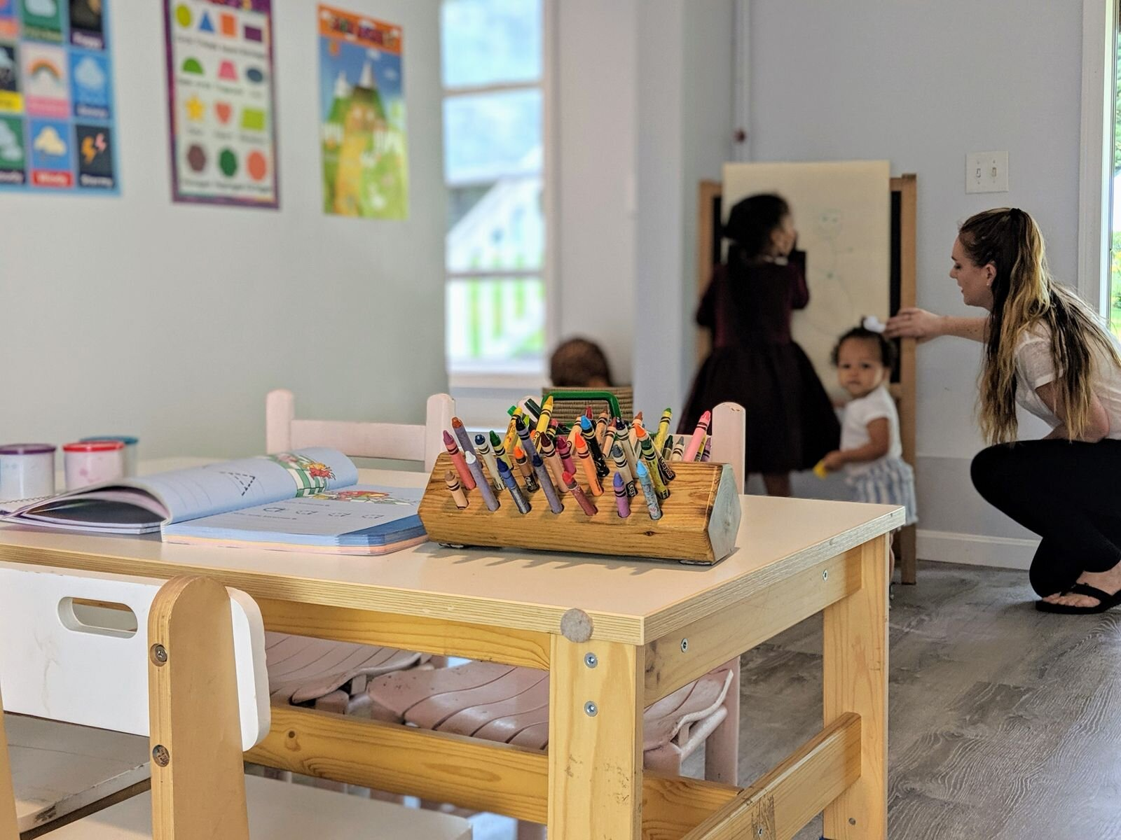 Ms. Lauren plays with the children at her new daycare in Leominster