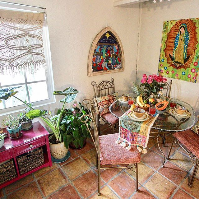 A bountiful harvest in this boho apartment ! Love the sunny interior with the pinks & plants & Spanish tile! Table & chairs repainted & reupholstered. Storage Bench repainted & repurposed for plants. Original art by @evaweingarten #interiordesign #interiordecorating #pink #boho #bohochic #plants #tassels #refurbished #tablescaping #macrame #spanishtiles #reupholstery #religiousart #handforgediron  #Etsy:Paulineluxurypillows