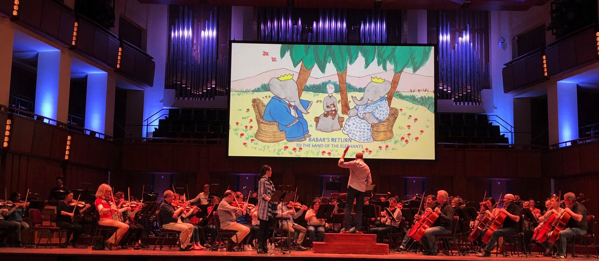 Rehearsal for the first U.S. performance of  Babar's Return to the Land of the Elephants  by the National Symphony Orchestra, Kennedy Center, Washington, DC, April 3, 2019  Steven Reineke conductor, Regina Aquino narrator. Jean de Brunhoff watercolor from the Kendra and Allan Daniel Collection, used with permission  Photo: Raphael Mostel