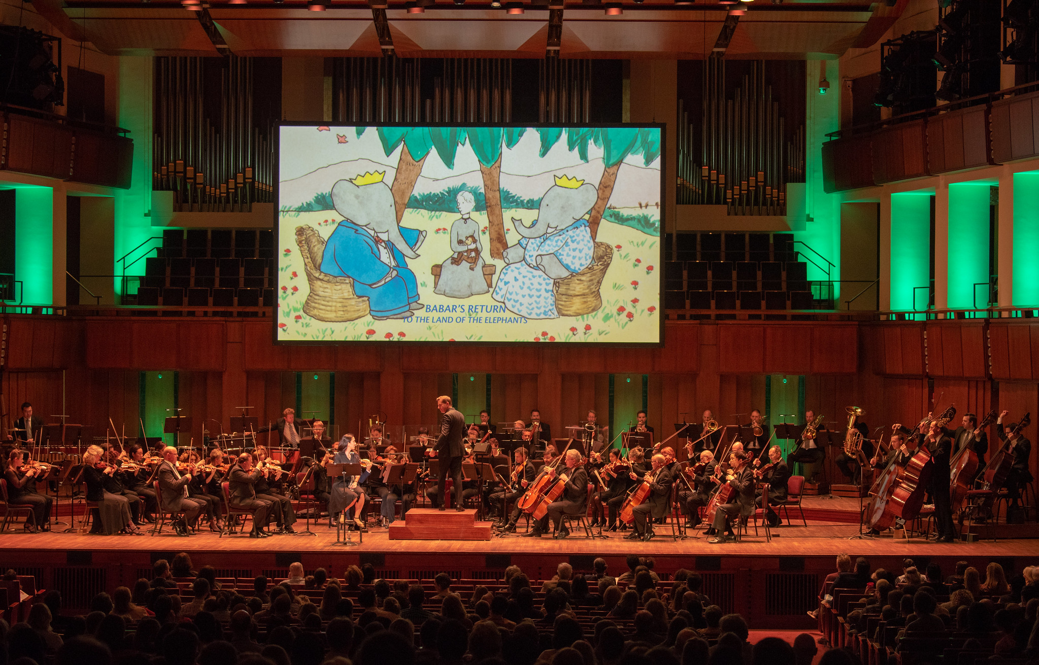 First U.S. performance,   Babar's Return to the Land of the Elephants   National Symphony Orchestra, Steven Reineke, conductor, Regina Aquino, narrator, John F Kennedy Center for the Arts, Washington, D.C., April 7, 2019  Photo: Erica Bruce for Mostel.com (full size, hi-res photo available). Multimedia image: original Jean de Brunhoff watercolor, Kendra & Allan Daniel Collection. Used with permissions