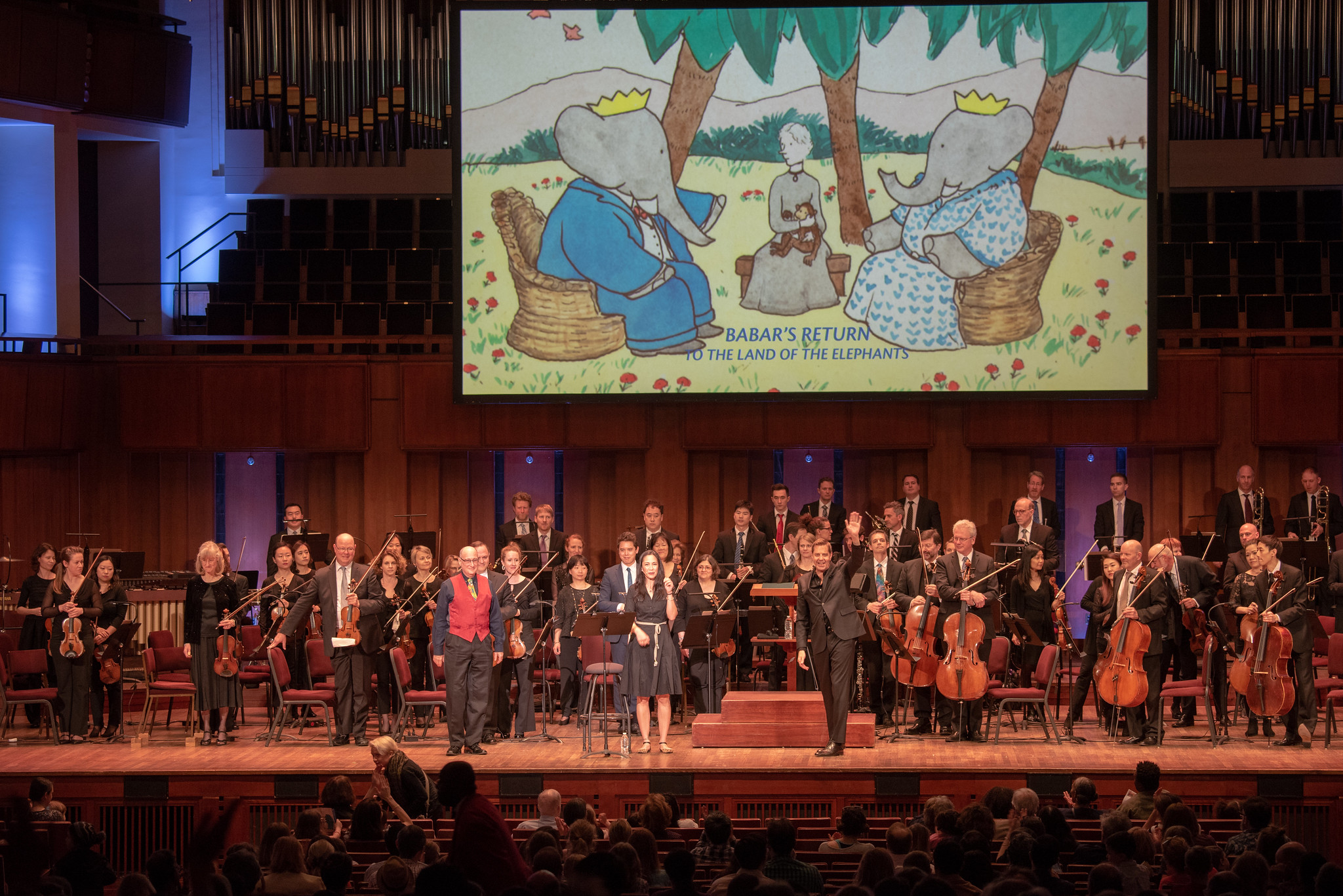 (l-r in front): Composer Raphael Mostel, narrator Regina Aquino, conductor Steven Reineke, bows after first U.S. performance,   Babar's Return to the Land of the Elephants   National Symphony Orchestra, John F Kennedy Center for the Arts, Washington, D.C., April 7, 2019  Photo: Erica Bruce (full size photo available). Multimedia image: original Jean de Brunhoff watercolor, Kendra & Allan Daniel Collection. Used with permissions