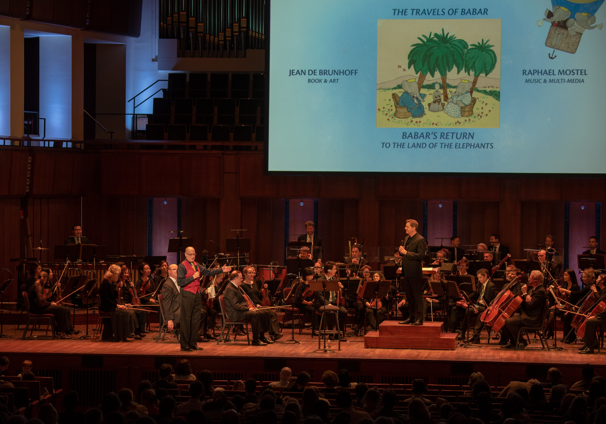 Composer Raphael Mostel and conductor Steven Reineke introducing the first U.S. performance of   Babar's Return to the Land of the Elephants   for orchestra, National Symphony Orchestra, John F Kennedy Center for the Arts, Washington, D.C., April 7, 2019  Photo: Erica Bruce for Mostel.com (full size, hi-res photo available). Multimedia images: original Jean de Brunhoff watercolors, Collection Bibliothèque nationale de France, and Kendra & Allan Daniel Collection. Used with permissions