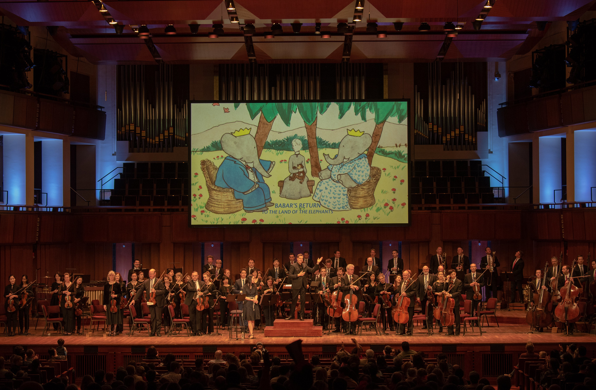 First U.S. performance, Raphael Mostel / Jean de Brunhoff   Babar's Return to the Land of the Elephants   for orchestra. Narrator Regina Aquino, conductor Steven Reineke with National Symphony Orchestra, John F Kennedy Center for the Arts, Washington, D.C., April 7, 2019  Photo: Erica Bruce, for Mostel.com (full size, hi-res photo available). Multimedia image: Jean de Brunhoff watercolor from the Kendra and Allan Daniel Collection, Used with permissions