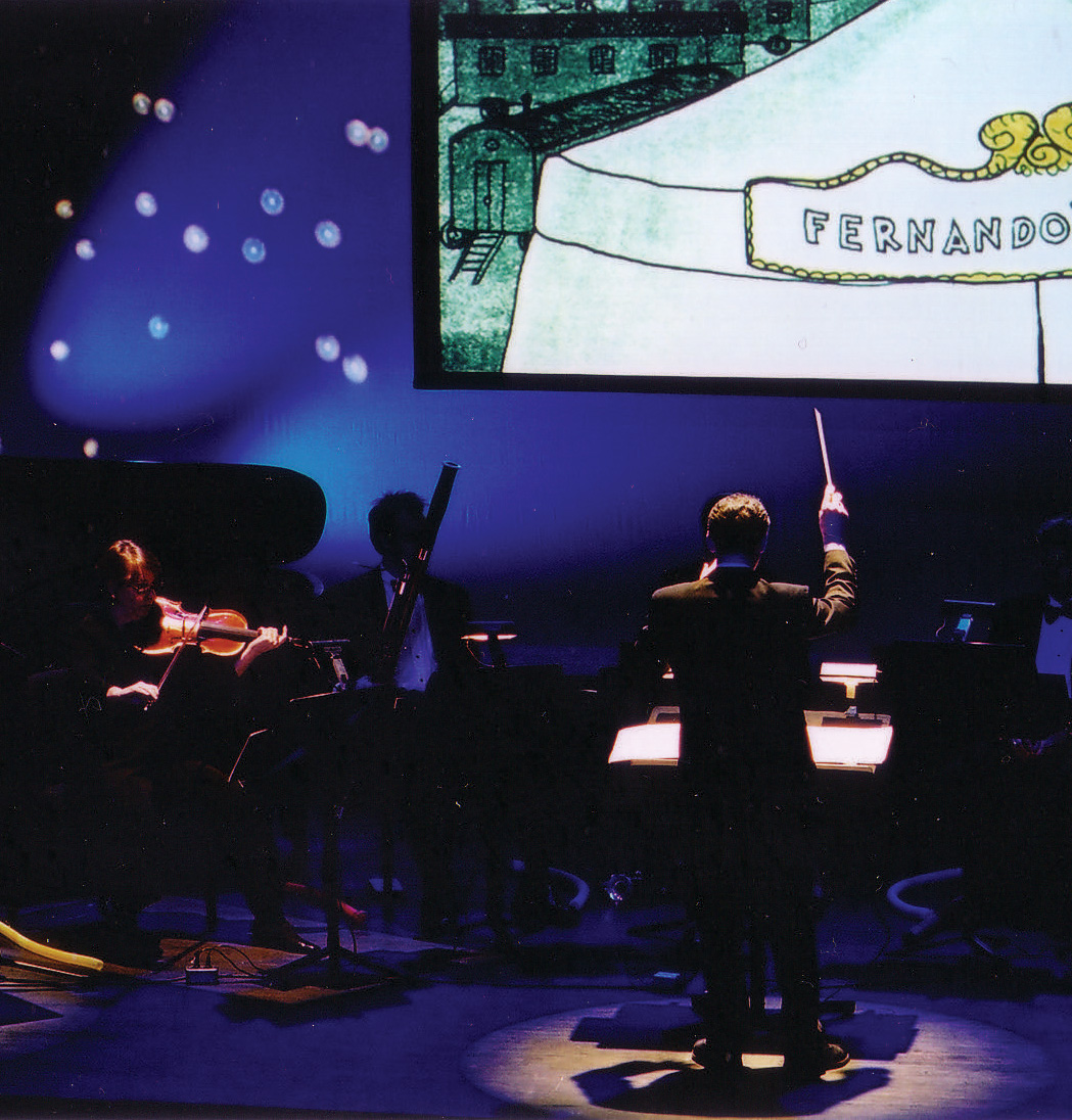 The full production of the original 8-musician scoring includes theatrical lighting that uses the intimacy to highlight the music-making as it is happening and harmonizes it with the visuals. Here, a viola solo in a night-time scene. Viola, Aurora Manuel, Alan R Kay, condcutor. Photo: Jay Muhlin for Source Music, Inc.