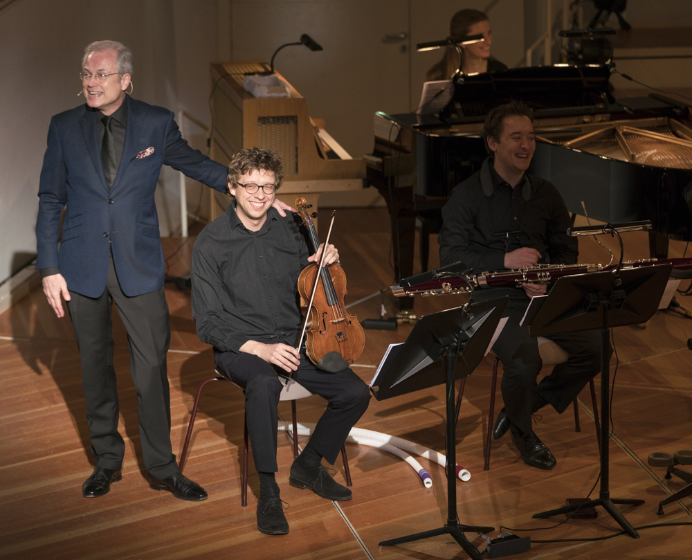The intimacy of the chamber version allows the introduction of each of the musicians one by one at the beginning, who then demonstrate the sound of their instruments with a short passage from the score. Here, narrator Hans-Jürgen Schatz introduces violist Martin von der Nahmer in the spotlight. Also pictured: bassoonist Paul-Gregor Staka and pianist Helen Collyer. World premiere of the new full production of the complete  Babar auf Reisen,  presented by the Berliner Philharmoniker in the Kammermusiksaal of the Berlin Philharmonie. Photo: Kai Beinert