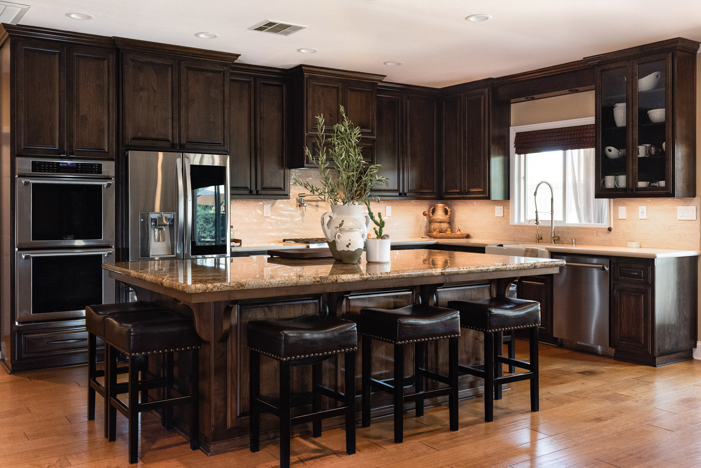 Traditional Mediterranean l-shaped kitchen with dark wood stained cabinets and island