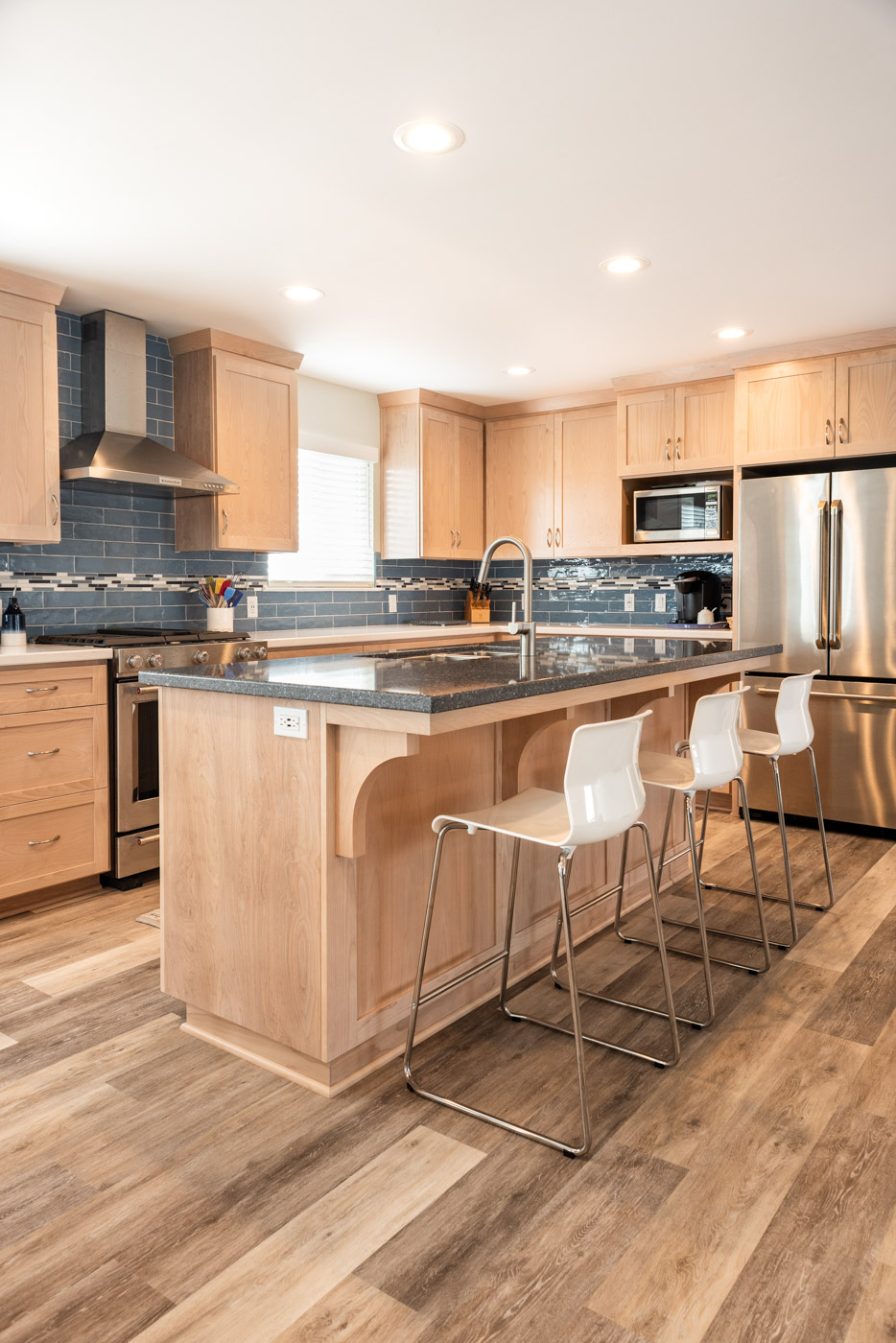 Coastal Contemporary custom kitchen cabinets with natural wood stain and island bar seating