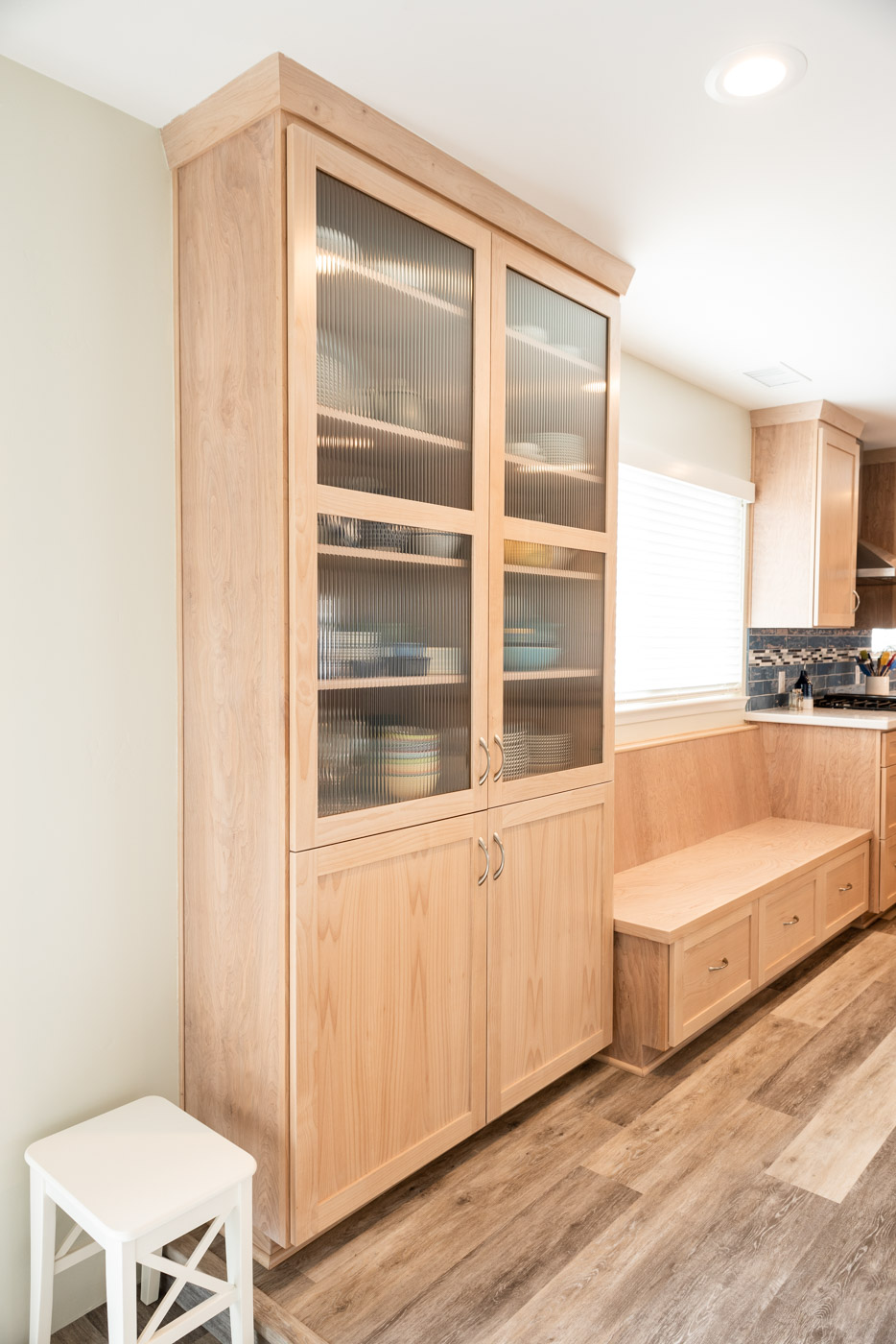 Coastal Contemporary custom kitchen cabinets with natural wood stain and glass display cabinet