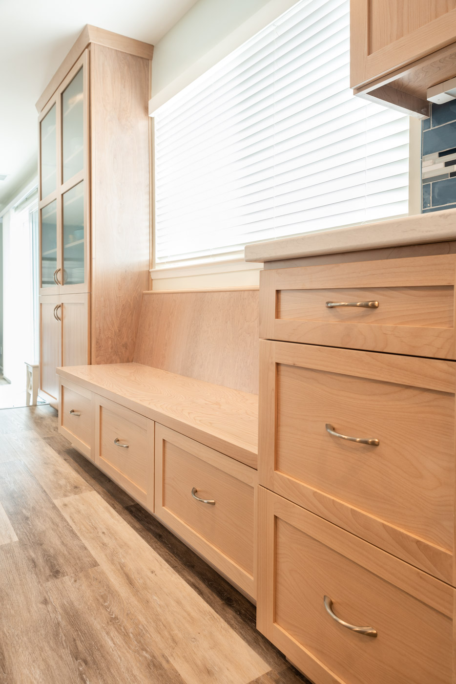 Coastal Contemporary custom kitchen cabinets with natural wood stain and custom built in bench