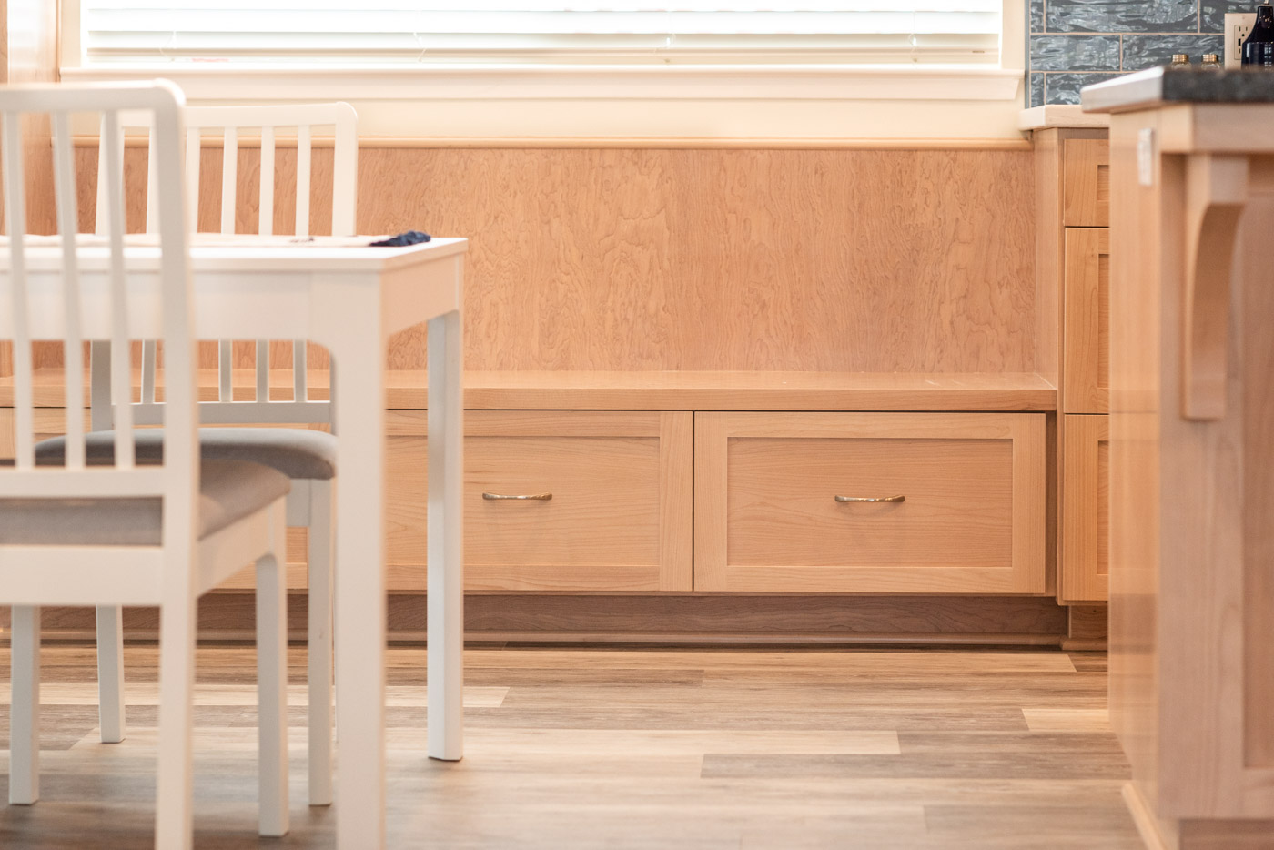 Coastal Contemporary custom kitchen cabinets with natural wood stain and built in bench