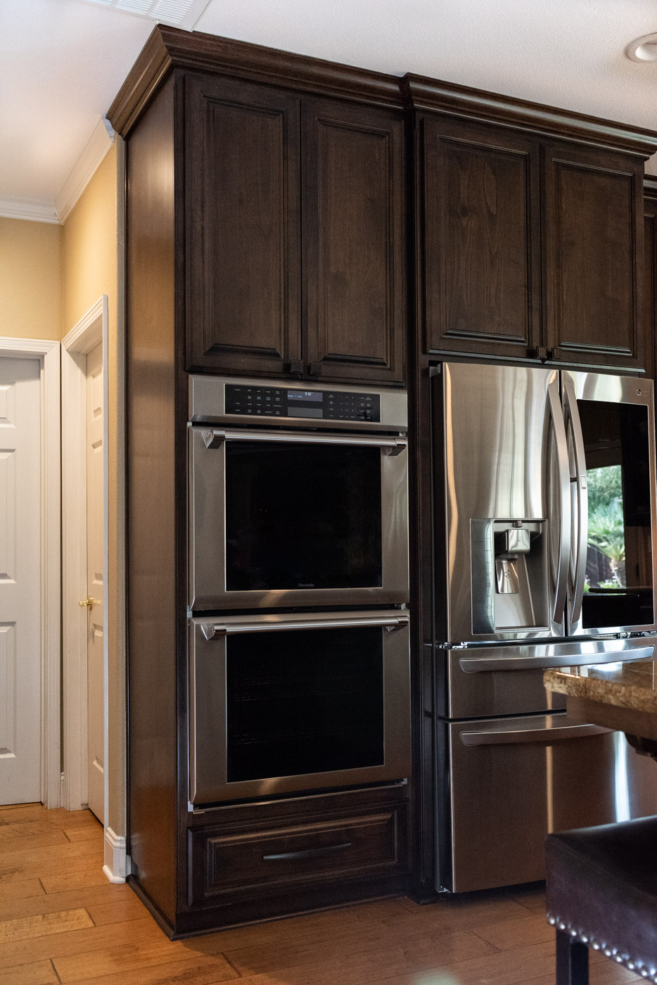 Traditional Mediterranean kitchen with dark wood stain cabinets and double oven