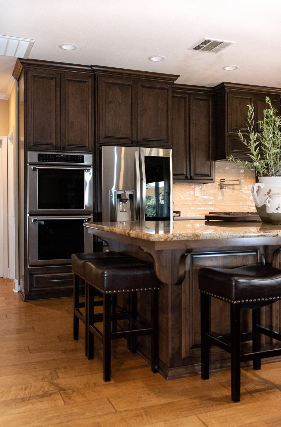 Traditional Mediterranean kitchen with dark wood stain cabinets and double ovens
