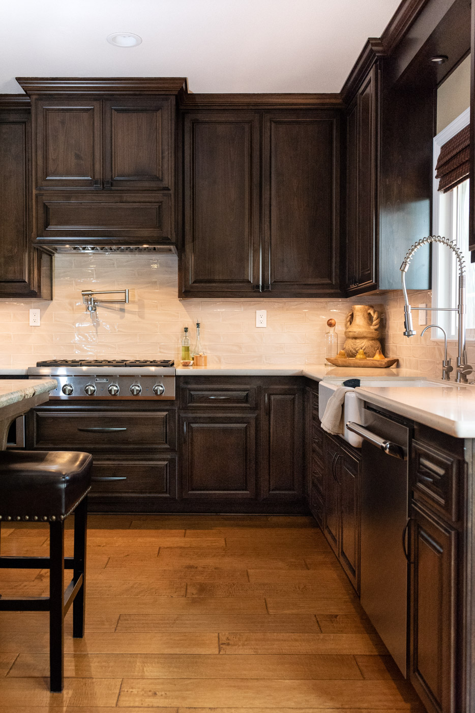 Traditional Mediterranean kitchen with dark wood stain cabinets and custom range hood
