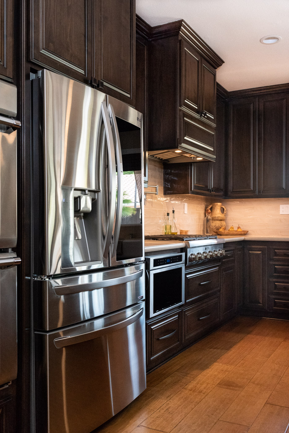 Traditional Mediterranean kitchen with dark wood stain cabinets and stainless steel appliances