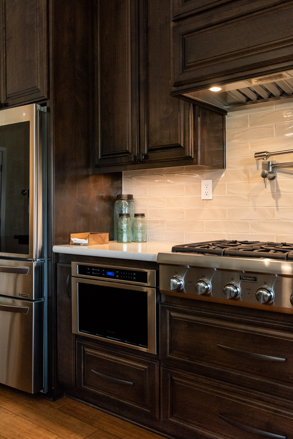 Traditional Mediterranean kitchen with dark wood stain cabinets and custom microwave storage