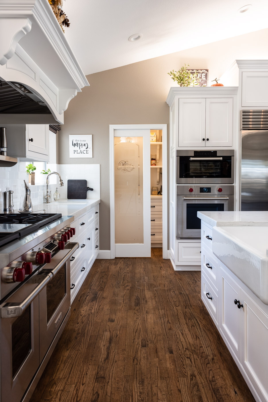 Transitional Country Cottage style kitchen with white recessed panel painted cabinets and custom pantry door