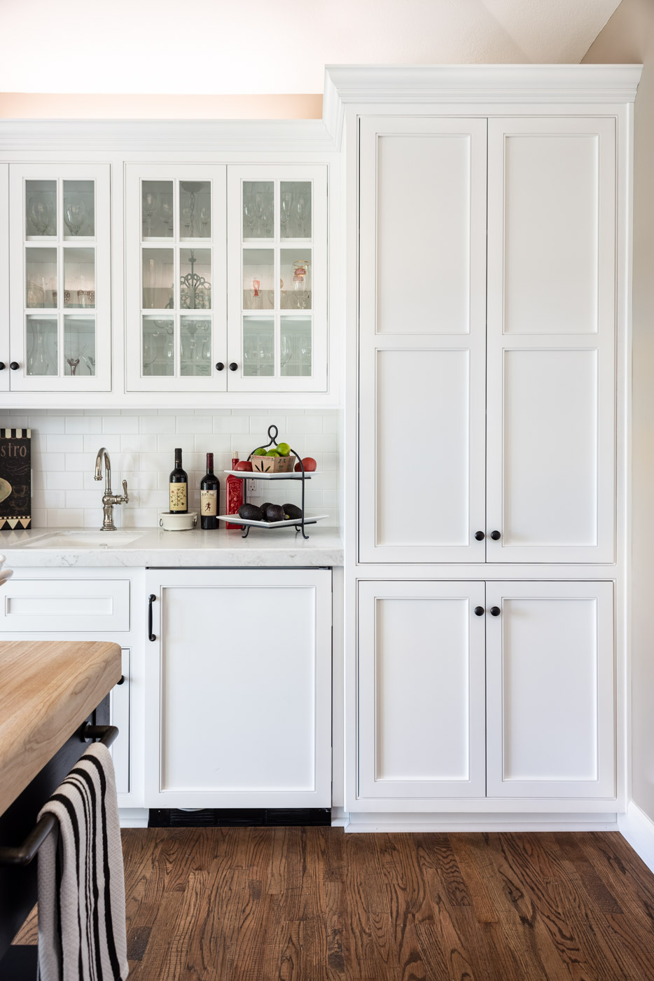 Transitional Country Cottage style kitchen with white recessed panel painted cabinets and refrigerator door panel
