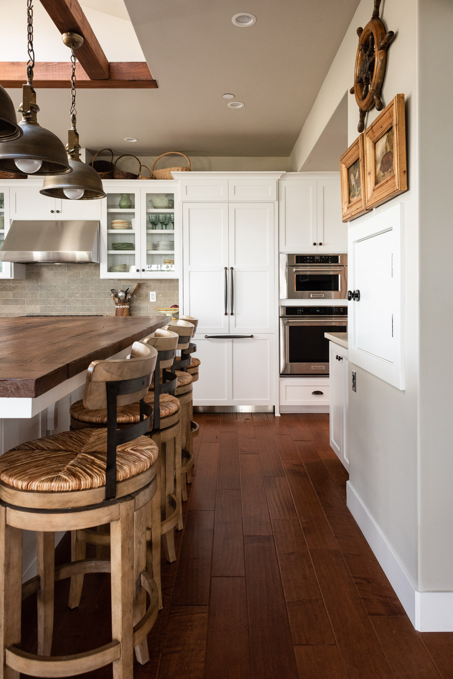 Coastal Craftsman kitchen with custom white painted shaker cabinets and refrigerator door panel