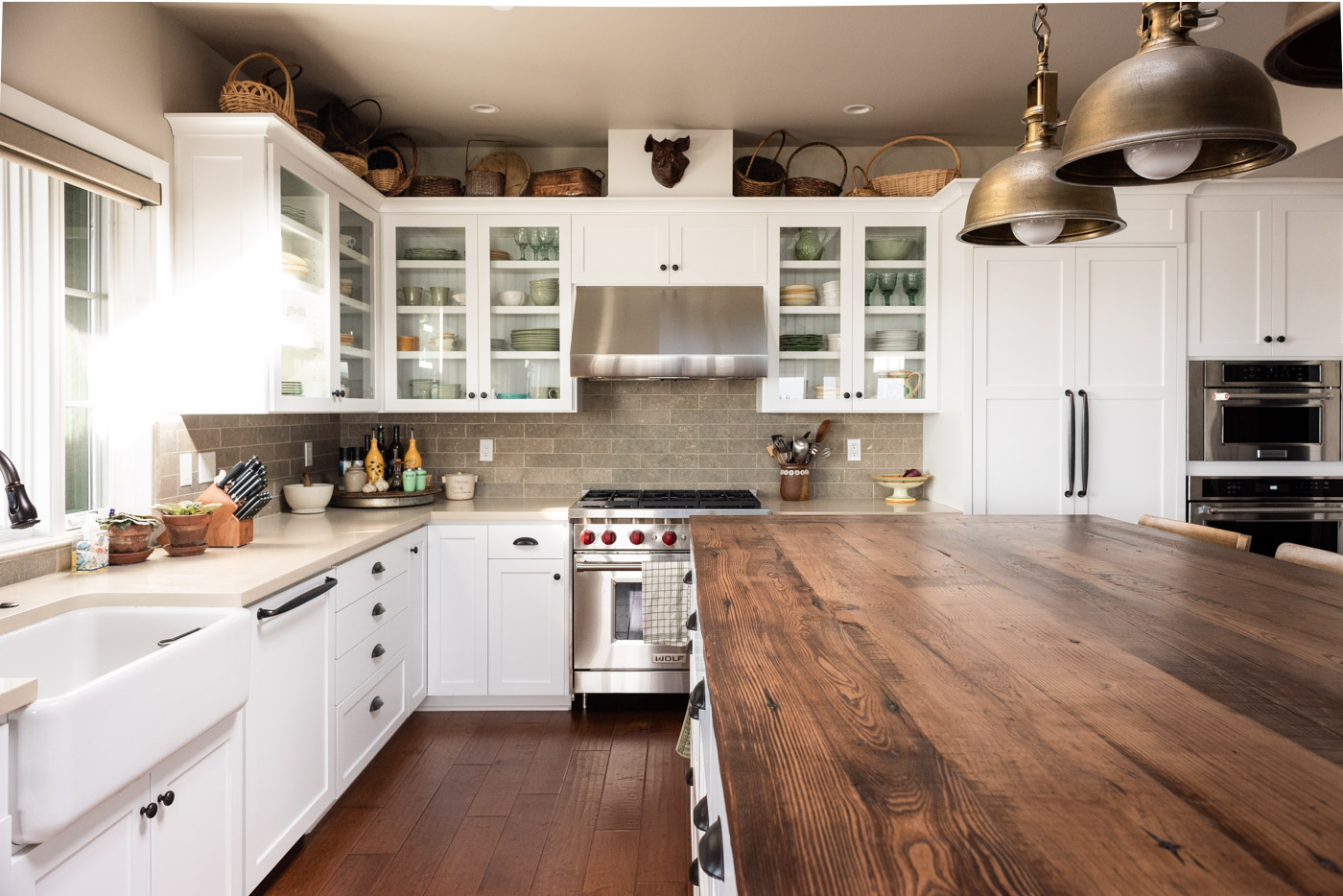 Coastal Craftsman kitchen with custom white painted shaker cabinets and wood butcher block counter top