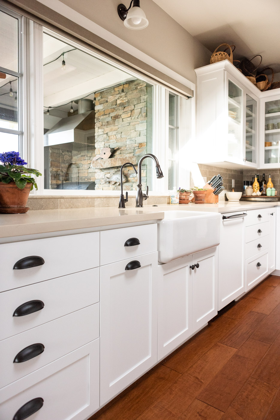 Coastal Craftsman kitchen with custom white painted shaker cabinets and farmhouse sink