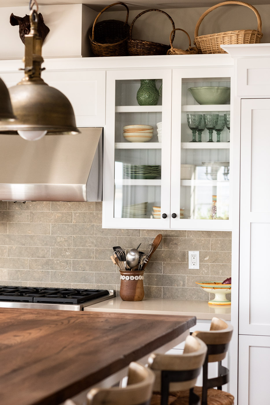 Coastal Craftsman kitchen with custom white painted shaker cabinets and glass door panels