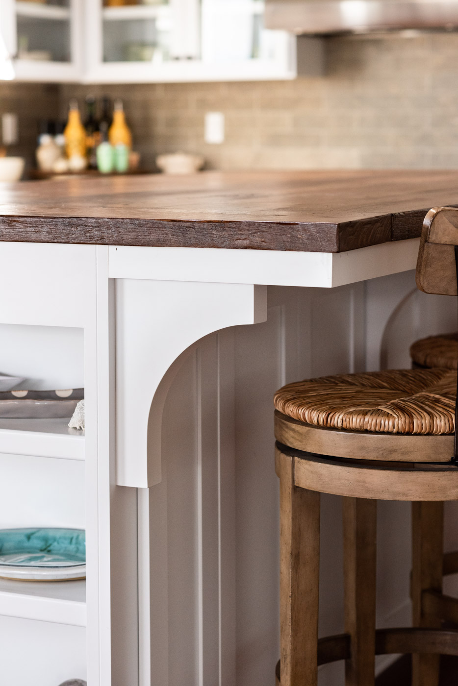 Coastal Craftsman kitchen with custom white painted shaker cabinets an corbels