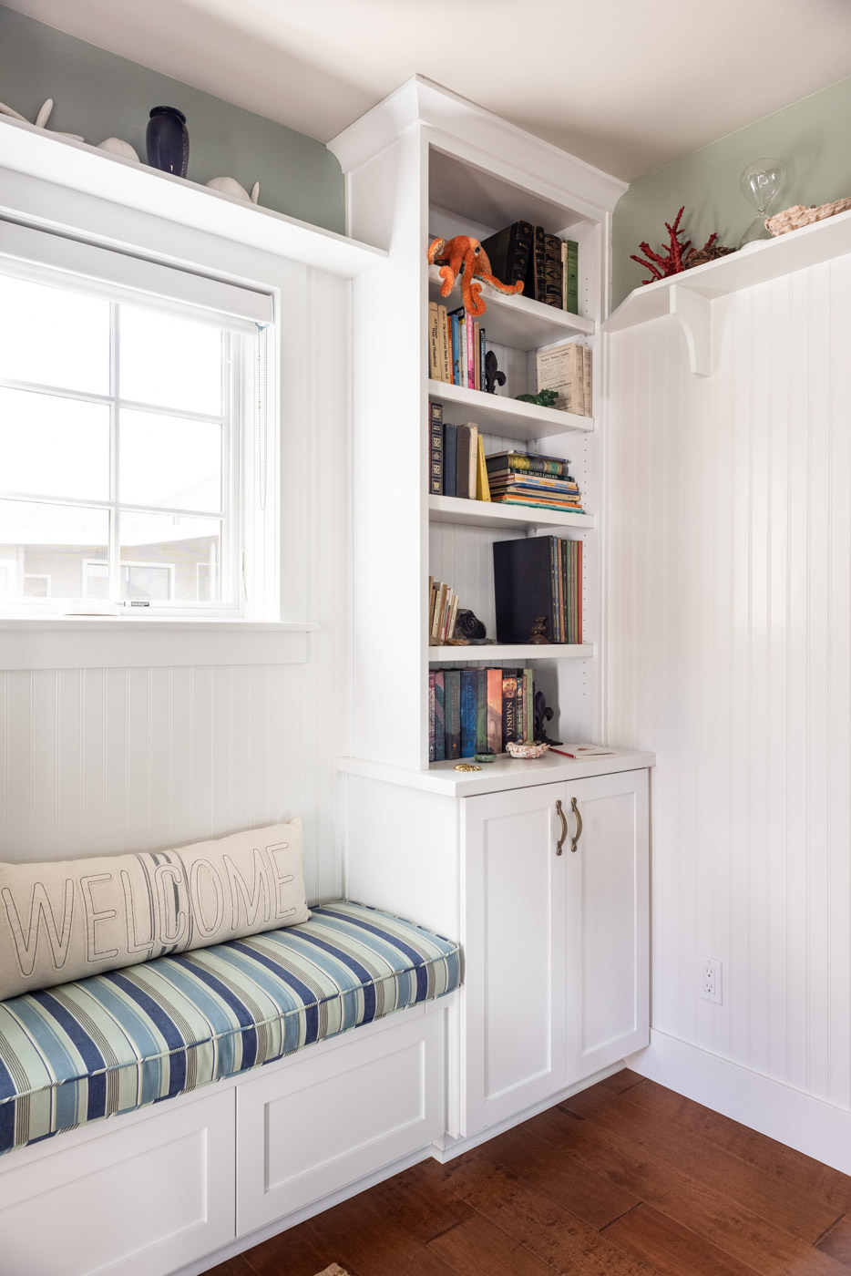 Coastal Craftsman home with custom white painted built in bookcase cabinets shelving