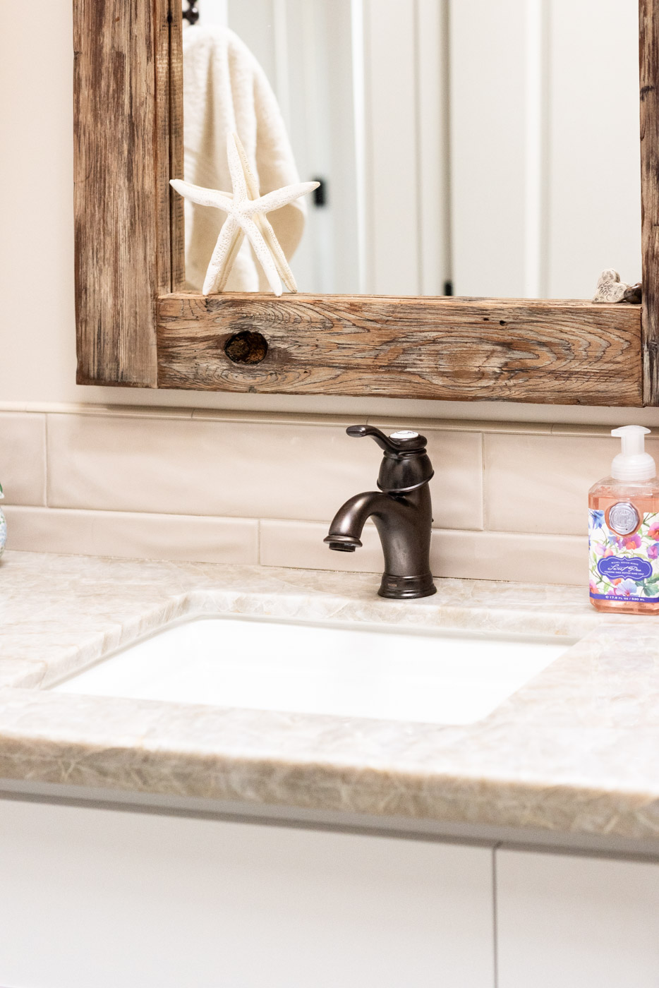 Coastal Craftsman home with custom white painted bathroom vanity cabinets and stone counter tops