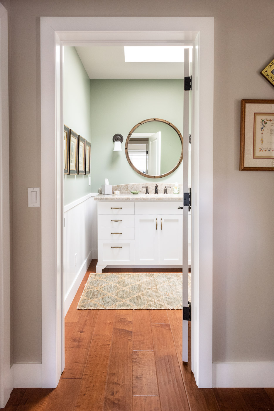 Coastal Craftsman home with custom white painted bathroom vanity cabinets