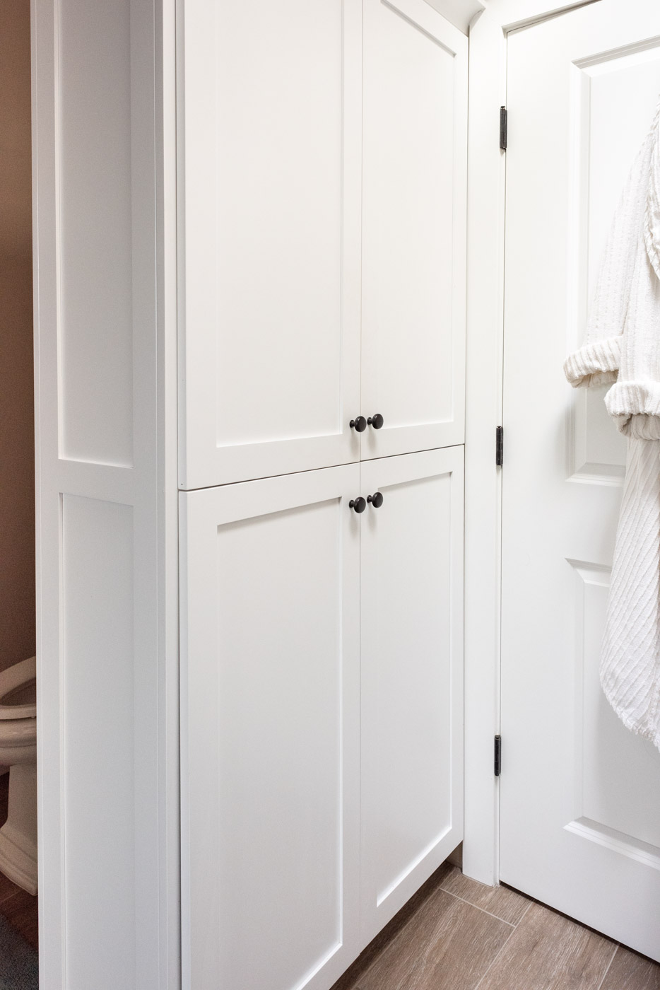 Coastal Craftsman home with custom white painted bathroom linen closet cabinets